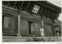 Chinese man standing in front of a temple