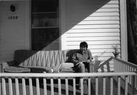 Student reading on the front porch of 1008 Park Street