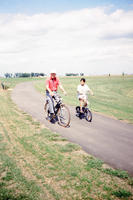 Elderly Man and Young Girl on Bikes
