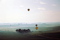 Three Hot Air Balloons Over Fields