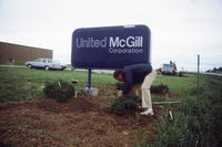 Man Planting Shrubs by United McGill Sign