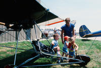 Father with Three Children Looking at a Glider Plane
