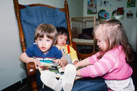 Three Children in a Rocking Chair at Grinnell Community Daycare Center