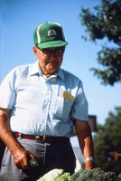 Man in a Green Hat Holding Produce