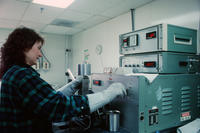 Woman with Gloves on at Machine
