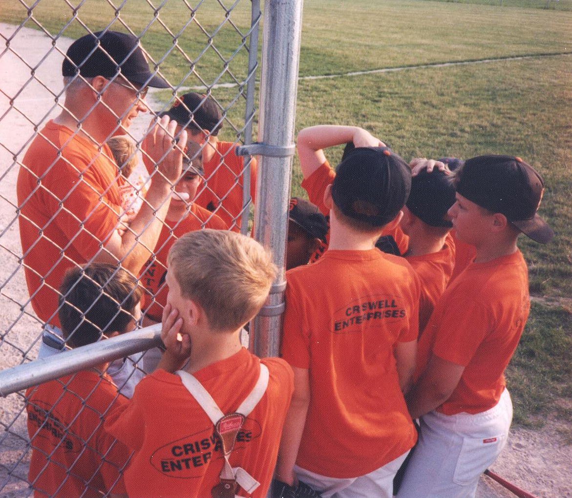 David Brandt, coaching little league. son Josiah (the hatless catcher) and his teammates listen to a pep-talk. Photo courtesy of Bridget Brandt