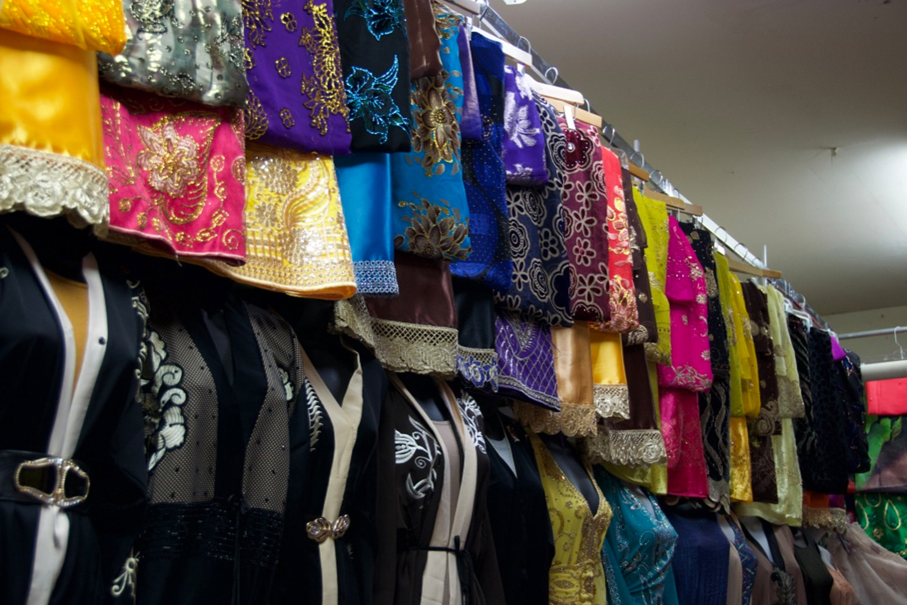 An array of colorful abaya, a style of dress worn by many Muslim women, line one wall of this market stall