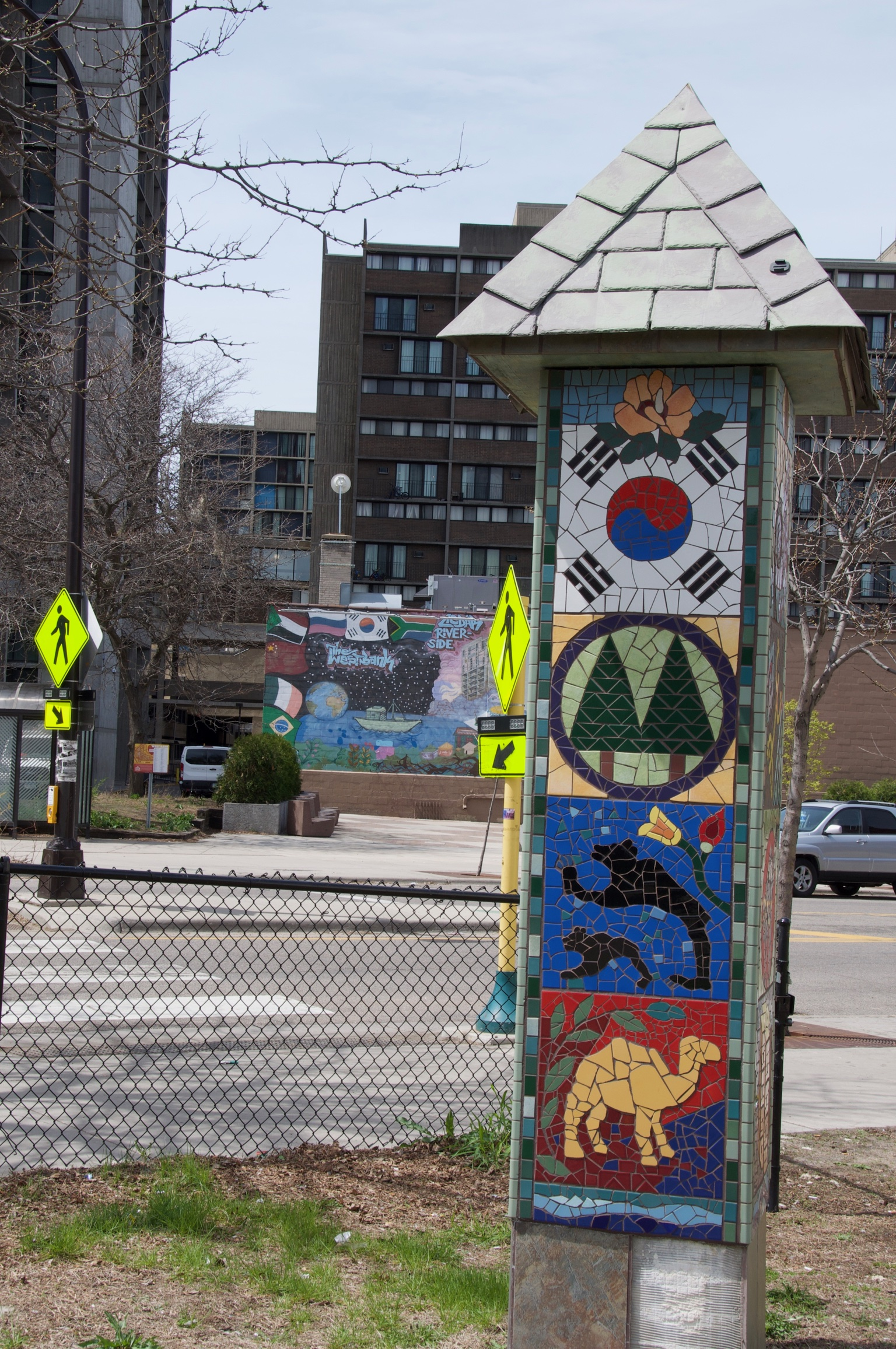 The mosaic signpost features images from varied cultures and environments