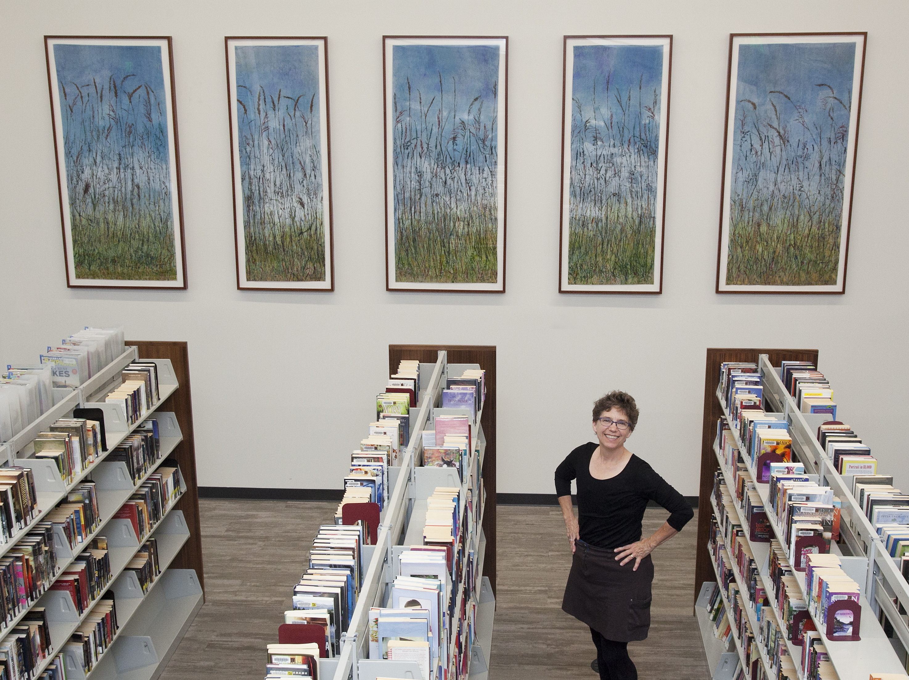 Snouffer with her installation, titled *Grass Lake* (botanical printmaking on pigment-infused tissue paper, 2017) at the Shoreview Branch Library in Shoreview, MN. It is her largest piece yet, and is named for a nearby prairie