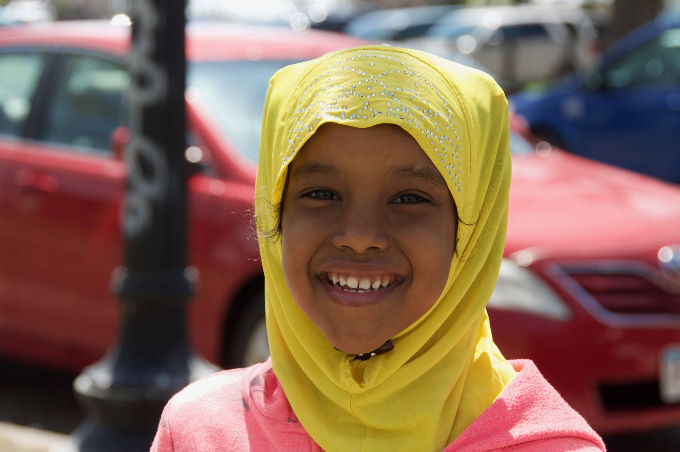 A beautiful young girl in a bright hijab accompanies her mother on errands
