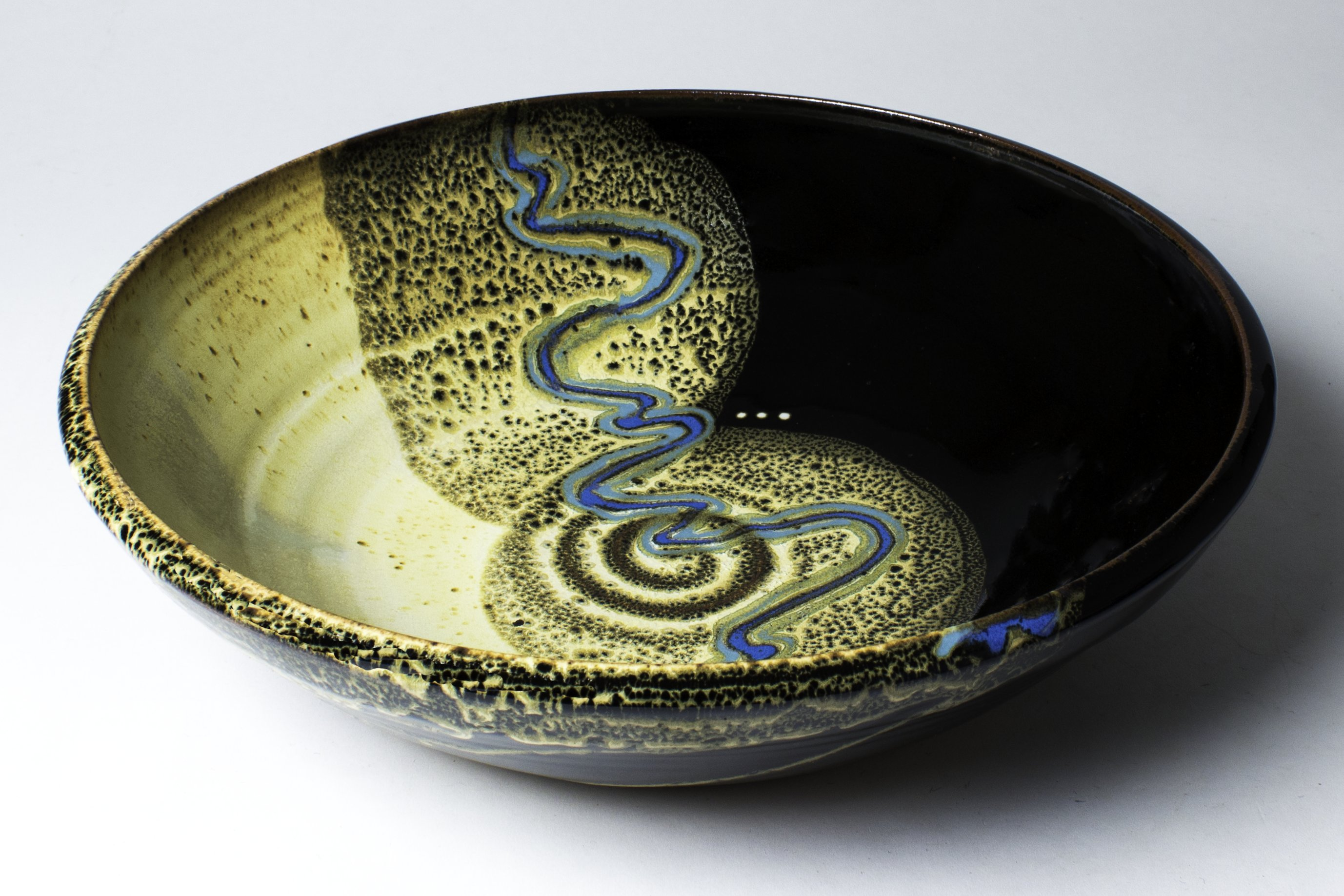 Smith grinds her own glazes from locally available minerals. Her primary ingredients include silica, feldspar, talc, red iron oxide and cobalt. This piece is glazed in her 'Yellow-stone' pattern