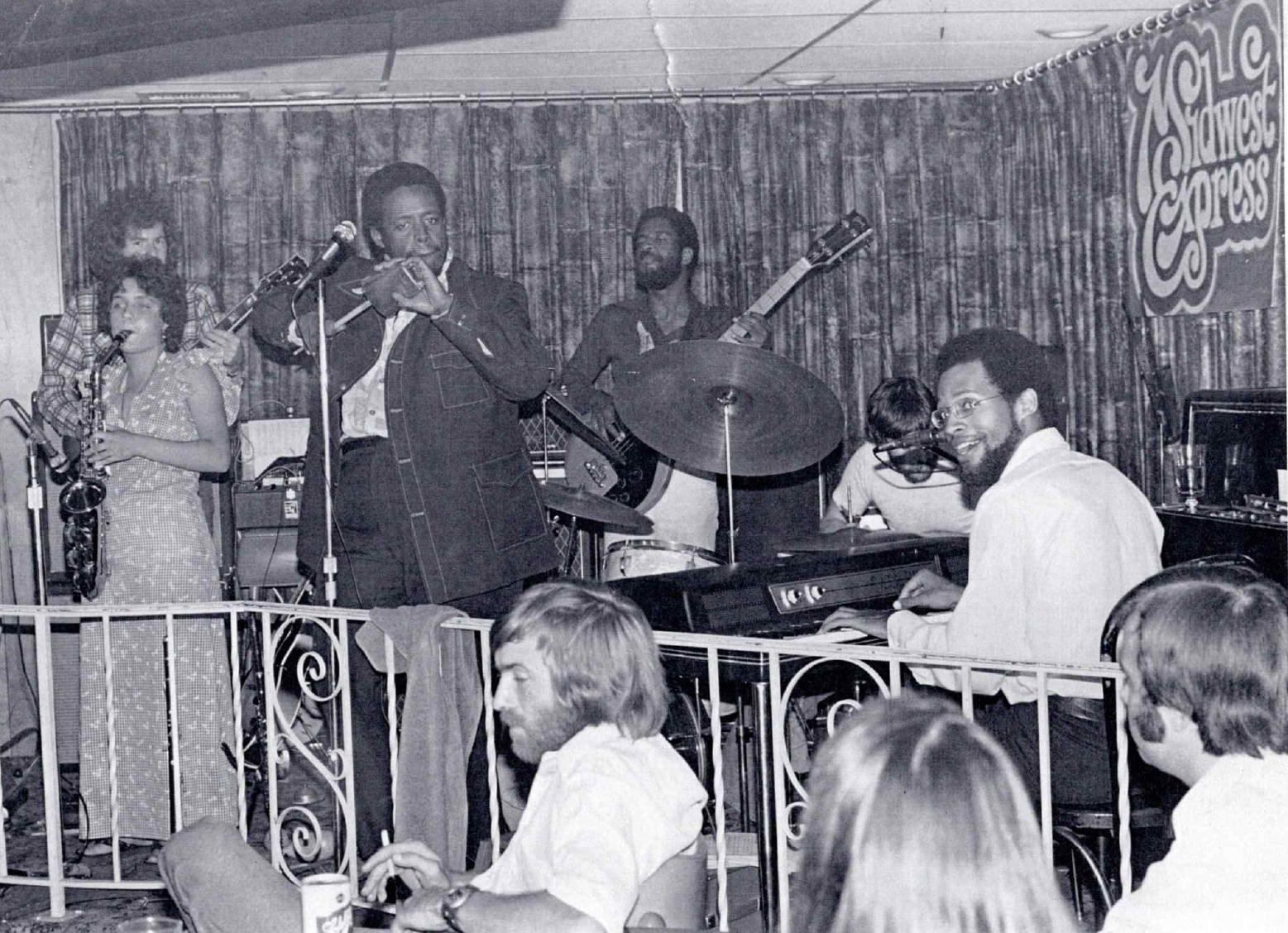 Midwest Express playing a gig in 1976. From far left, Marcia Miget is on saxophone, with Danny Nicholson behind her on guitar and Big Mike Edwards next to her at the mic. Dartanyan Brown (against the back wall) is on bass, John Grguric is on drums, and Bobby Parker is seated at the keyboard