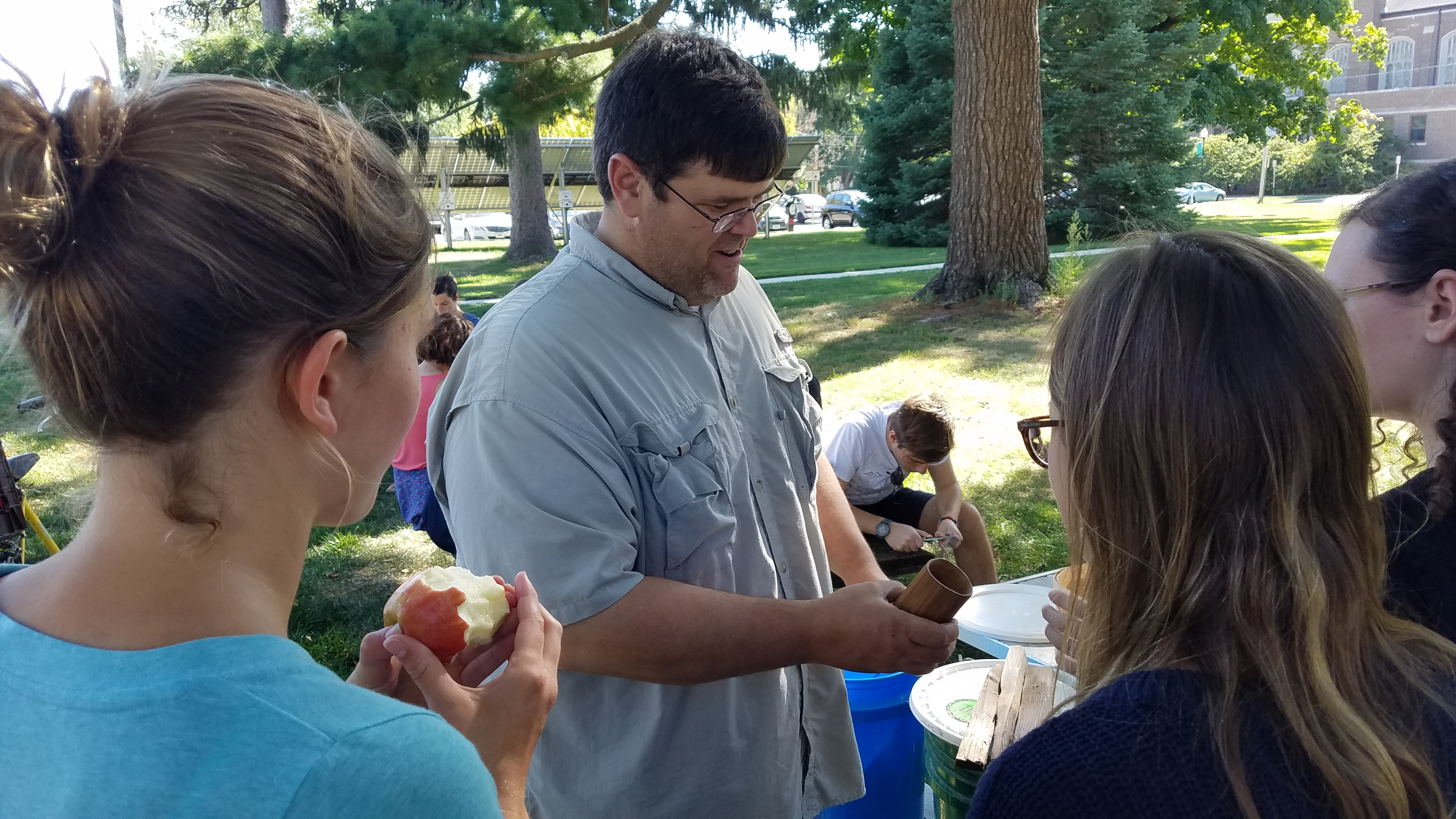 Chris Blair, co-founder of the College's carving group, instructing some new carvers at the College Garden.