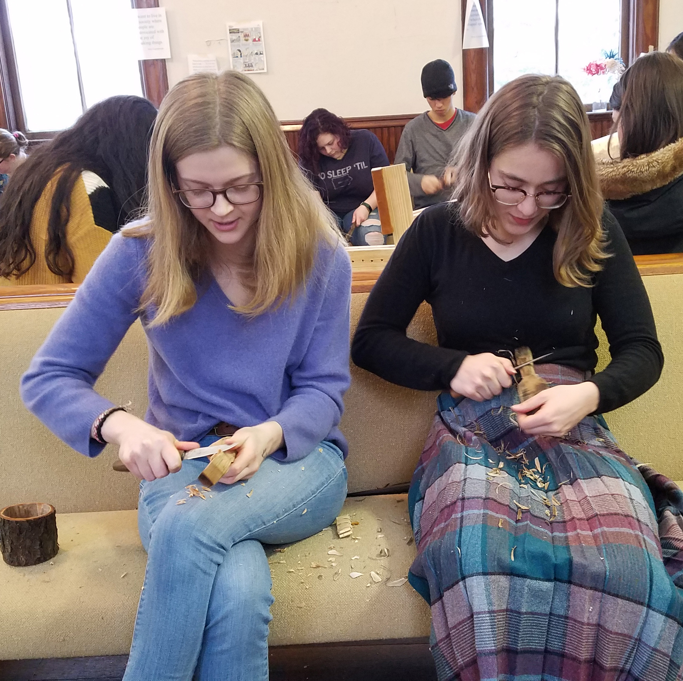 Two friends chatting and carving using thumb push (on left) and pull stroke (on right).