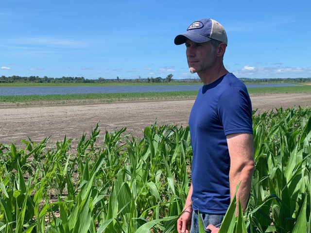 Corey McIntosh stands at the edge of Missouri River floodwaters near his home in July 2019. Photo courtesy of Corey McIntosh